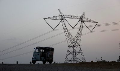 A auto rickshaw move past power transmission tower at Hub about 25 km (15 miles) northwest of Karachi, Pakistan, 18 June 2010 (Photo: Reuters/Akhtar Soomro).