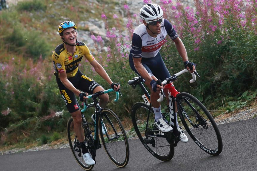 Australia's Richie Porte wearing white rides up a French peak, mouth open as another cyclist smiles from behind.