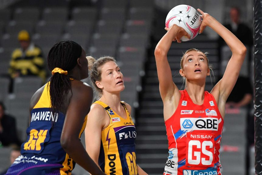 A NSW Swifts Super Netball player holds the ball above her head as she prepares to shoot for goal against the Lightning.