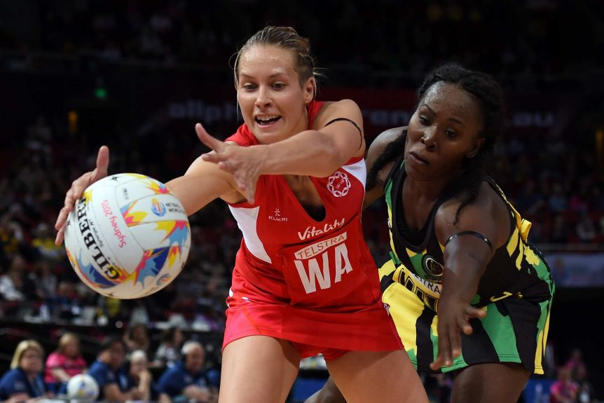 A netballer reaches out to grab the ball, as a defender leans down and extends her hand to stop her.