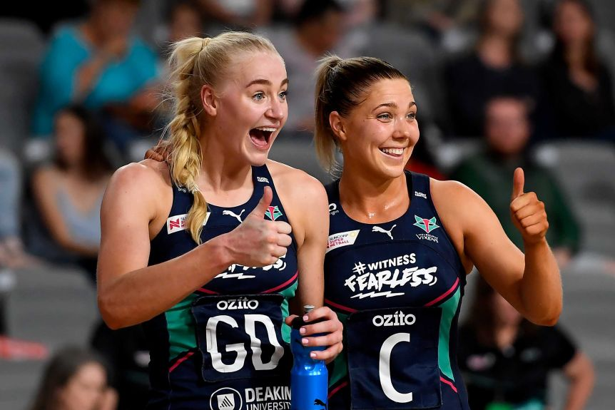 Two Melbourne Vixens Super Netball players give the thumbs up as they smile after beating NSW Swifts.