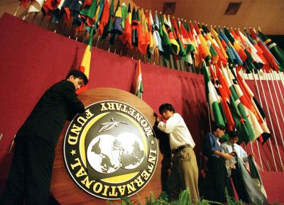 Workers remove the International Monetary Fund (IMF) emblem and nation flags from the podium after a World Bank/IMF ceremony in Hong Kong (Photo: Reuters).