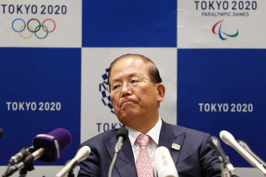 A serious looking Tokyo Olympics executive sits in front of microphones during a press conference.