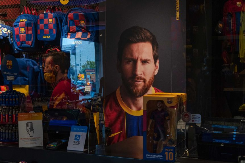 A Lionel Messi poster and action figure can be seen through a Barcelona team shop window.