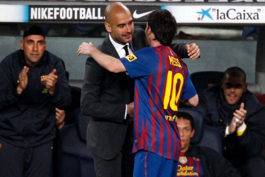 The Barcelona manager leans in to hug his star player on the sidelines during a La Liga game.