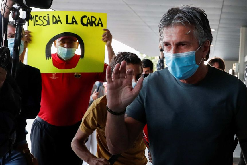A man wearing a mask holds his hand up as he stands in front of a camera in an airport.