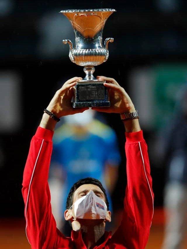 Novak Djokovic holds a trophy aloft while wearing a face mask.