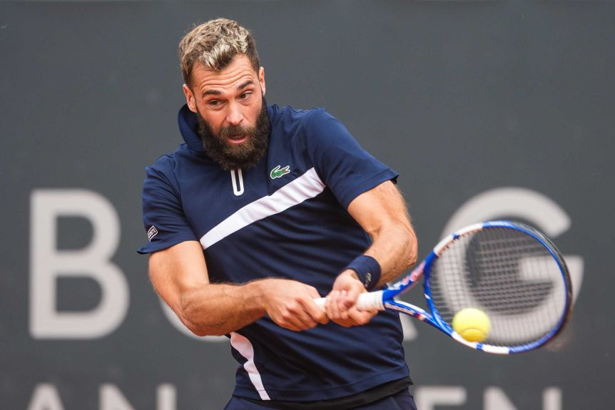 Benoit Paire opens his mouth and plays a two-handed back hand shot wearing a dark blue polo shirt