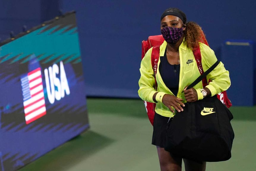 Serena Williams wears a facemask while walking past an on-court hoarding with her name on it