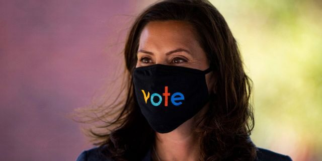 "Michigan Gov. Gretchen Whitmer wears a mask with the word ""vote"" displayed on the front during a roundtable discussion on health care, Wednesday, Oct. 7, 2020, in Kalamazoo, Mich. (Nicole Hester/Ann Arbor News via AP)/"