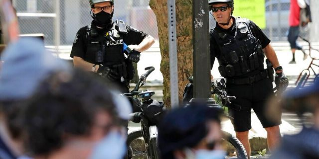 Police officers look on at protesters in Seattle on July 20, 2020. (AP Photo/Elaine Thompson, File)