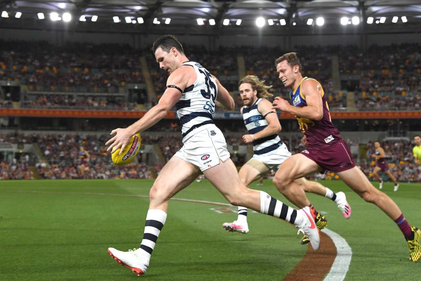 Running along the boundary line, Patrick Dangerfield drops the ball in preparation of a kick on his left foot