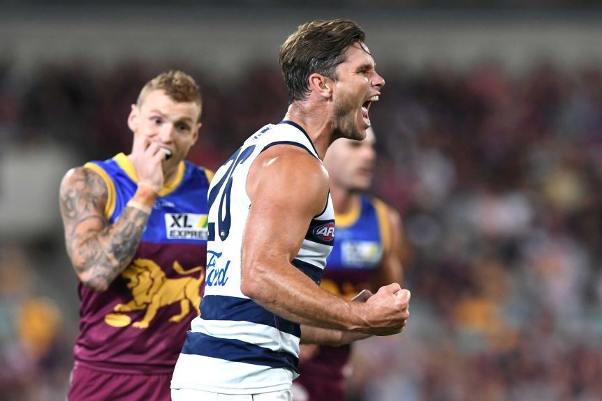 Geelong's Tom Hawkins shouts in celebration in front of Brisbane's Mitch Robinson.