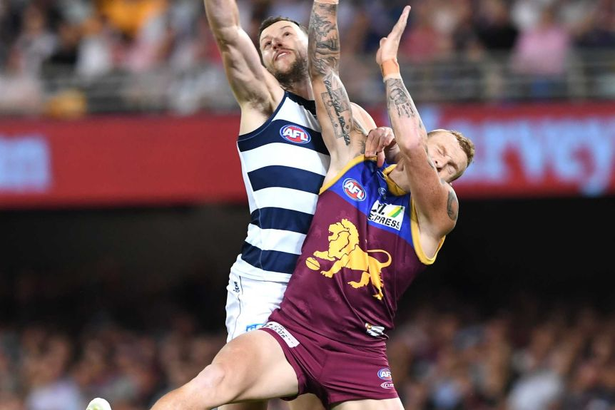Sam Menegola and Mitch Robinson crash into each other as they reach for the ball above their heads