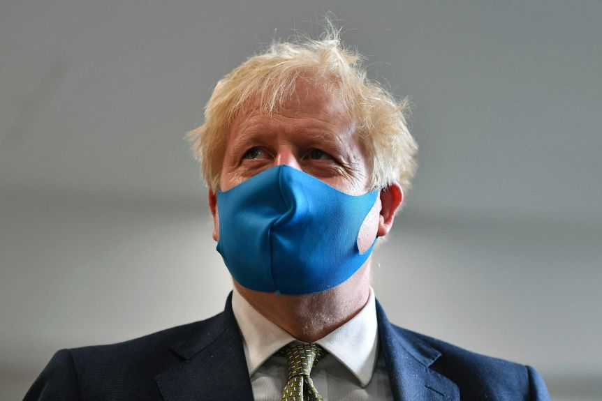 Britain's Prime Minister Boris Johnson wears a blue face mask.