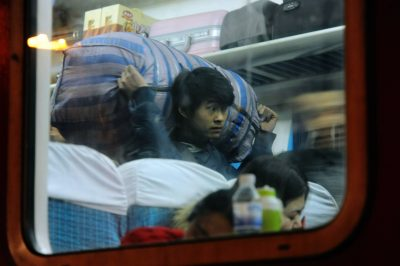 A Chinese migrant worker carries his luggage in a train as he heads back home for the Chinese Lunar New Year or Spring Festival at the Qingdao Railway Station in Qingdao City, east China's Shandong province, 13 February, 2015 (Reuters).