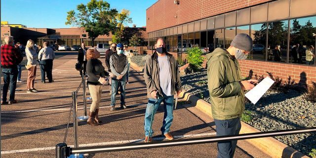 In this Sept. 8, 2020 file photo voters line up outside of the Minneapolis early voting center as Minnesota opened early voting for the general election. (AP Photo/Steve Karnowski, File)