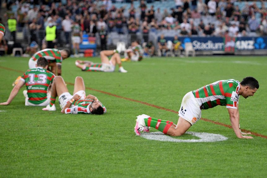 South Sydney Rabbitohs players are strewn across the grass after losing an NRL preliminary final against Penrith.