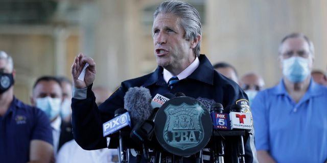 Surrounded by law enforcement and supporters, New York City PBA President Pat Lynch, center, speaks during a news conference in New York, Tuesday, June 9, 2020. (AP Photo/Seth Wenig)