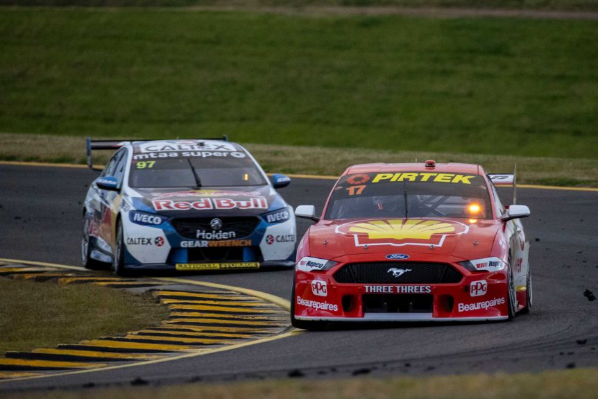 A red Ford Mustang with a number 17 in the window leads a white and blue Holden Commodore with Red Bull written on it