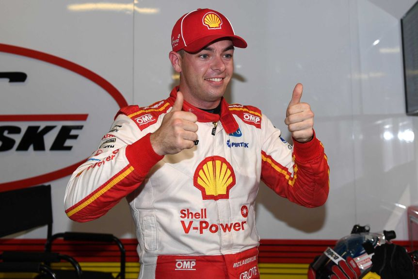 Scott McLaughlin, wearing his racing kit covered in advertising, smiles and gives two thumbs up.