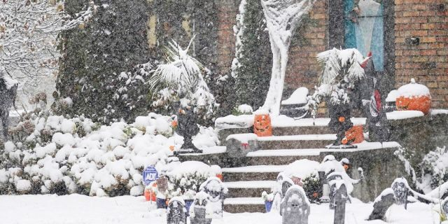 A Halloween display in Minneapolis receives the first measurable snow of the season as a storm arrived over much of Minnesota Tuesday, Oct. 20, 2020.