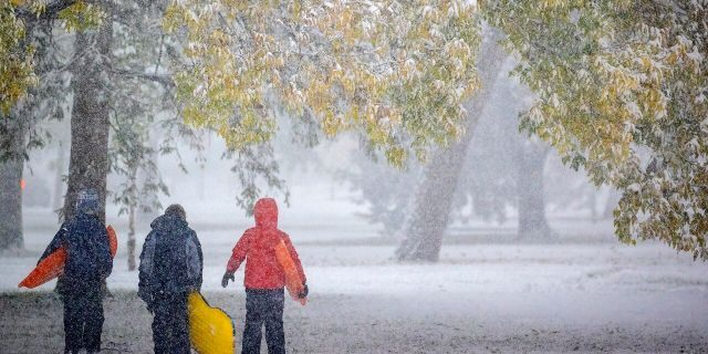Atticus Saunders, 13, left, Keller Lindstrom, 10, and Fritz Saunders, 11, make their way through the snow after sledding near Lake Nokomis, Tuesday, Oct. 20, 2020, in Minneapolis.