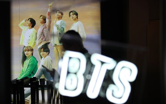 A woman walks past a photo of K-pop boy band BTS at an apartment store in Seoul, South Korea - Shutterstock