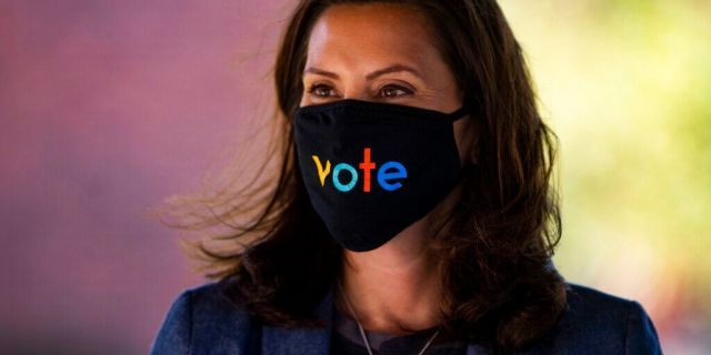 """Michigan Gov. Gretchen Whitmer wears a mask with the word """"vote"""" displayed on the front during a roundtable discussion on healthcare in Kalamazoo, Mich."""