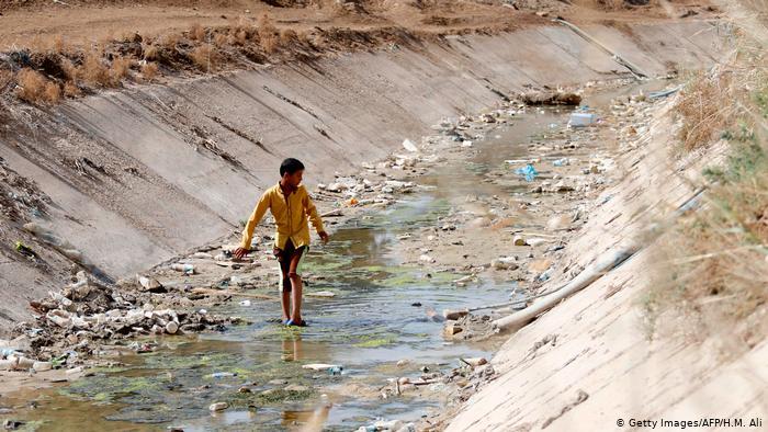 A boy walks through a dried up dyke in Iraq