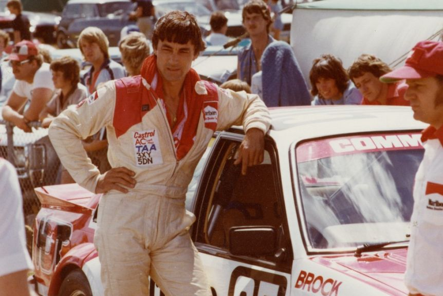 A man in overalls leans on a car with Brock written on it.
