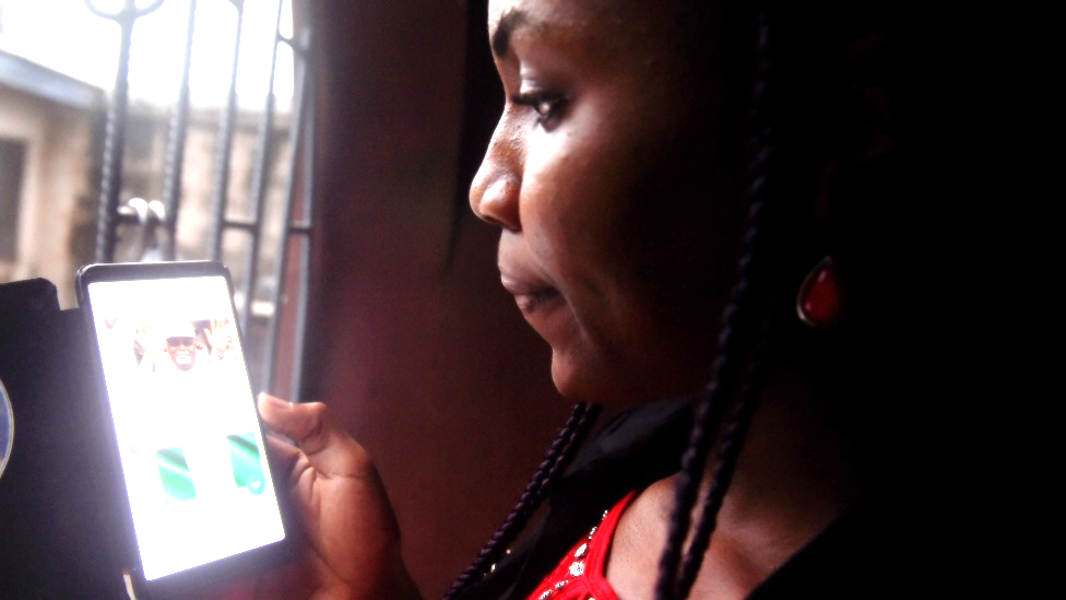 A woman looking at a mobile phone in Lagos, Nigeria - 2018
