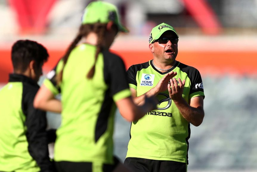 A cricket coach claps as his players get ready for a WBBL match.