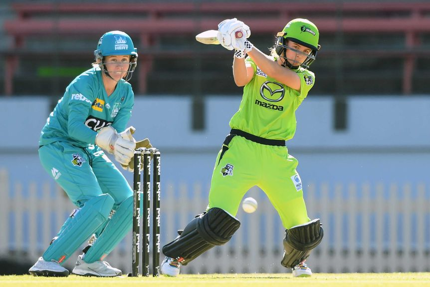 A Sydney Thunder WBBL player hits out to the leg side as the Brisbane Heat wicketkeeper looks on.
