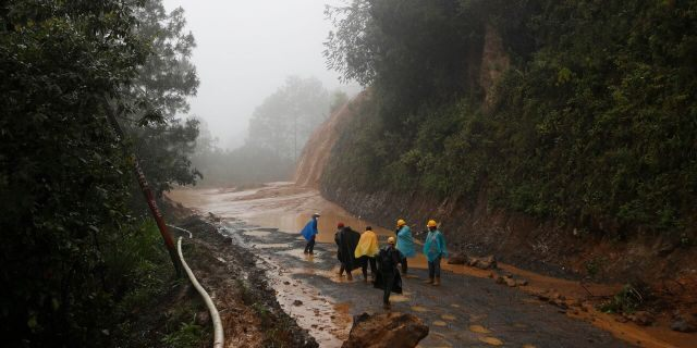 Workers walk around a road blocked by a landslide in San Cristobal Verapaz, Saturday, Nov. 7, 2020, in the aftermath of Hurricane Eta.