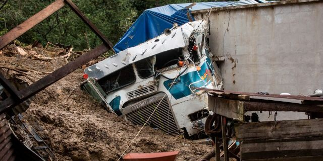 A semi is partially buried in a massive, rain-fueled landslide in the village of Queja, in Guatemala, Saturday, Nov. 7, 2020, in the aftermath of Tropical Storm Eta.
