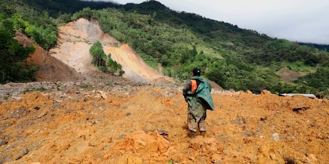 A member of a search and rescue team looks for survivors through the destruction caused by a massive, rain-fueled landslide in the village of Queja, in Guatemala, Saturday, Nov. 7, 2020, in the aftermath of Tropical Storm Eta.