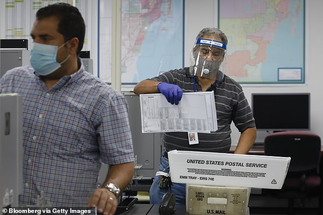 A worker wearing a protective mask collects mail-in ballots to scan from a U.S Postal Service bin at the Miami-Dade Elections Department in Florida.The postal service has said it had delivered 122 million blank and completed ballots before Tuesday