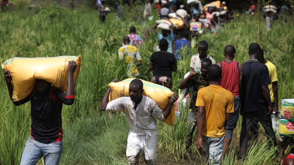 People carrying bags of grains
