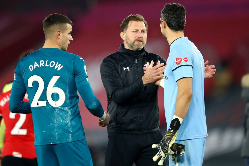 A tracksuited football manager clasps hands with a goalkeeper after a win in a Premier League game.